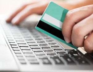 Hands with credit card on keyboard
